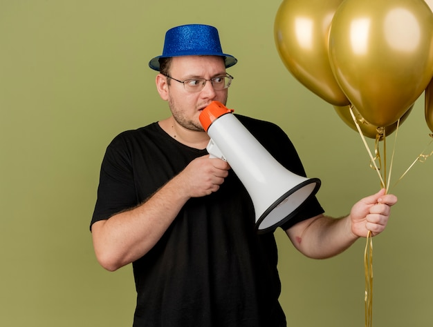 Uomo slavo adulto ansioso in occhiali ottici che indossa cappello da festa blu tiene e guarda i palloncini di elio che parlano nell'altoparlante