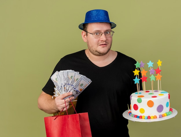 Anxious adult slavic man in optical glasses wearing blue party hat holds money gift box paper shopping bag and birthday cake