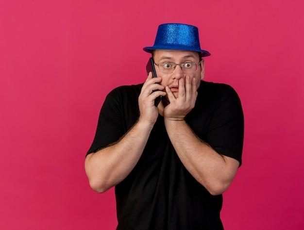 Ansioso uomo slavo adulto in occhiali ottici che indossa un cappello da festa blu mette la mano sulla bocca parlando al telefono on