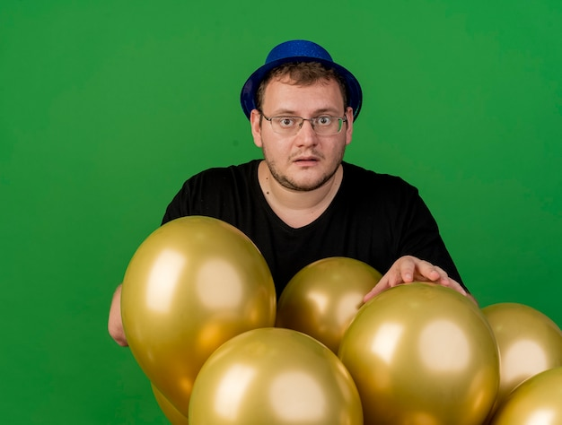 Anxious adult slavic man in optical glasses wearing blue party hat stands with helium balloons