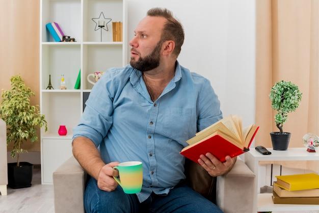Взволнованный взрослый славянский мужчина сидит на кресле, держа книгу и чашку, глядя в сторону внутри гостиной
