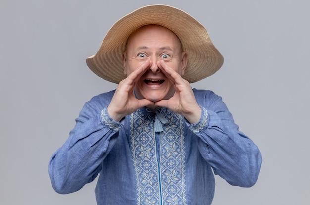 밀짚 모자를 쓰고 파란 셔츠를 입은 불안한 성인 슬라브 남자가 손을 입에 가까이 대고