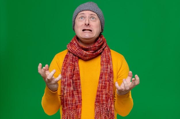 Взволнованный взрослый славянский мужчина в зимней шапке и шарфе на шее держит руки открытыми и смотрит вверх