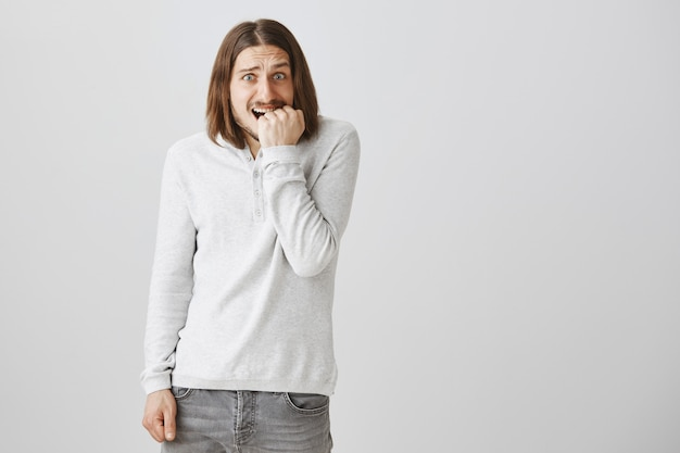 Anxious, alarmed guy shivering and biting fingernails in panic