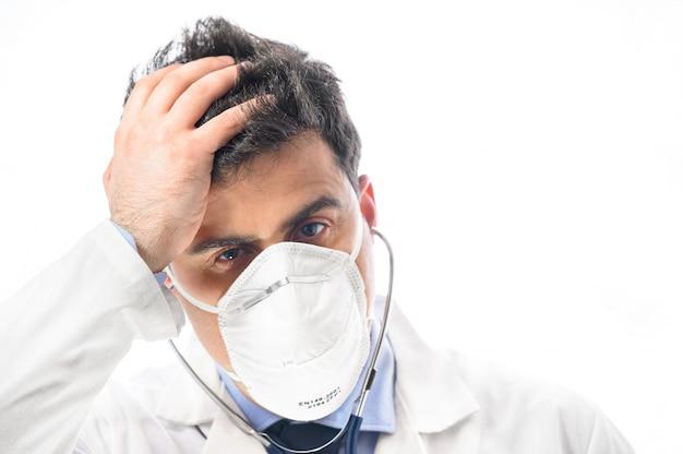 不安で神経質な医師。心配そうな表情の防護マスクを着た医師が頭に手を置いた医師の肖像画を閉じます。パンデミックコロナウイルスの発生。