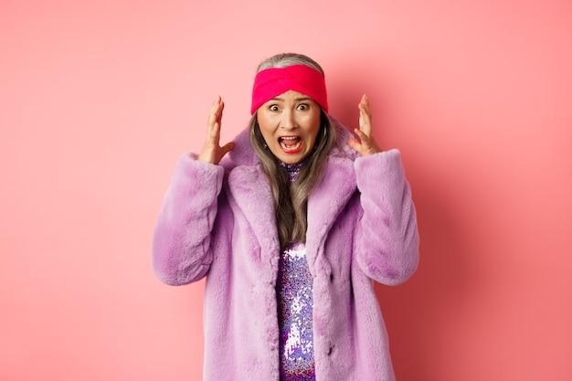 ピンクの背景の上に立って、叫び、握手し、カメラに警戒し、心配して叫んで、スタイリッシュなフェイクファーのコートを着た気になるアジアの年配の女性