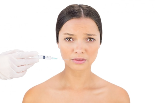 Anxious bare model having botox injection around mouth
