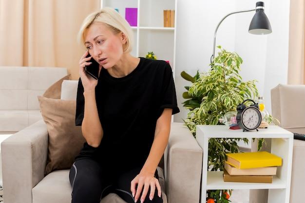 Bella donna russa bionda ansiosa si siede sulla poltrona parlando al telefono guardando a lato