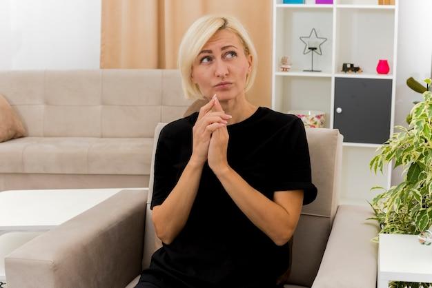 気になる美しい金髪のロシア人女性が椅子に座って手をつないで見上げる