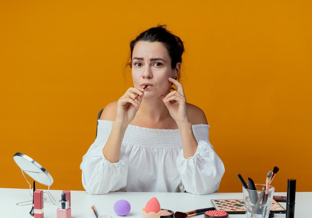 Anxious beautiful girl sits at table with makeup tools bites makeup brush isolated on orange wall