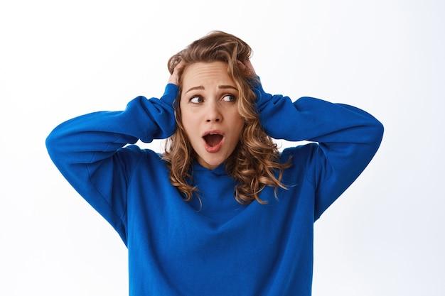 Ansiosa ragazza bionda in preda al panico, tenendosi per mano sulla testa e urlando allarmata, guarda da parte il testo promozionale con la faccia preoccupata travagliata, muro bianco