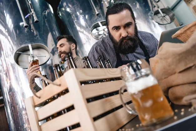 Anxious brewer inspecting beer in mug at factory