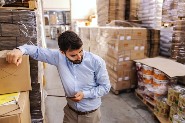 Anxious businessman standing in warehouse and holding tablet and thinking how to solve a problem.