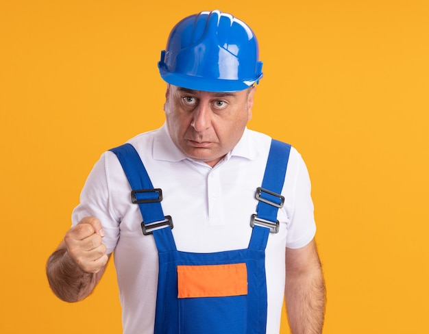 L'uomo adulto caucasico ansioso del costruttore in uniforme tiene il pugno sull'arancia