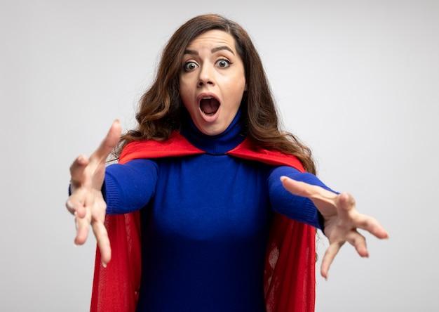 Ragazza ansiosa del supereroe caucasico con mantello rosso che allunga le mani isolate sulla parete bianca con lo spazio della copia