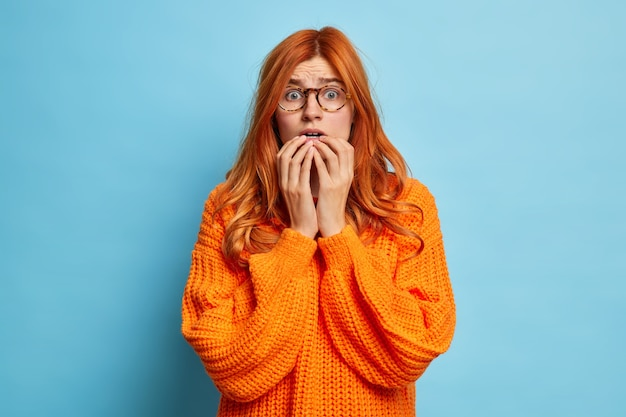 Anxious concerned disappointed redhead woman has terrible feared look holds breath as found out what happened hears bad horrible news dressed in knitted orange jumper.
