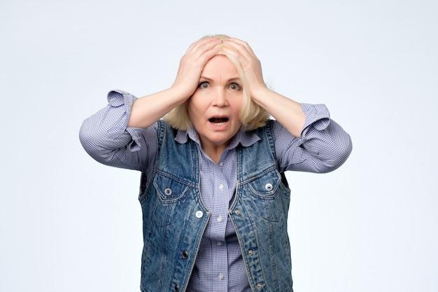 欲求不満なストレス表現を持っている心配している高齢者のブロンドの女性