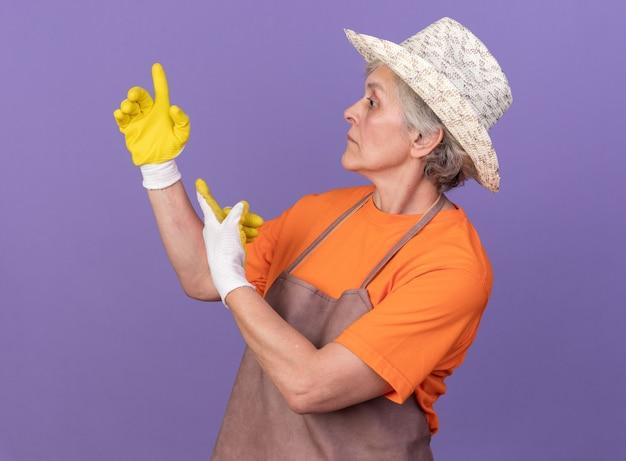 원예 모자와 장갑을 착용하는 불안한 노인 여성 정원사