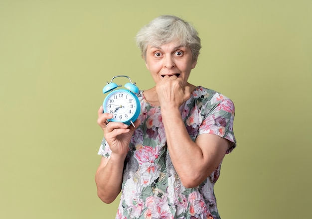La donna anziana ansiosa morde il pugno che tiene sveglia isolata sulla parete verde oliva