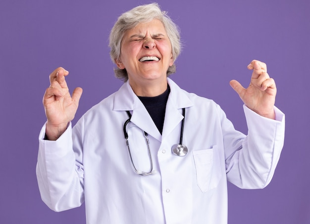 Anxious elderly woman in doctor uniform with stethoscope stands with crossed fingers
