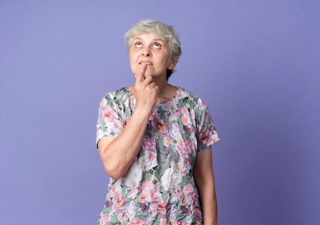 気になる年配の女性が紫色の壁に孤立して見上げる口に指を置く