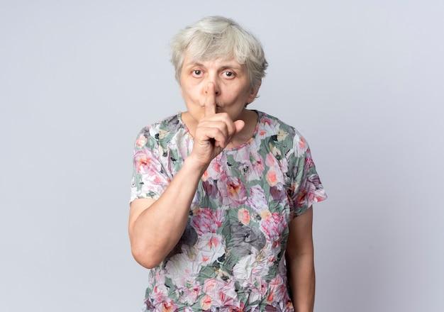 気になる年配の女性が白い壁に分離された静けさの静かなサインを身振りで示す口に手を置く