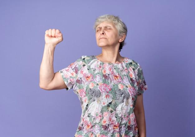 気になる年配の女性が紫色の壁に隔離された目を閉じて拳を上げる