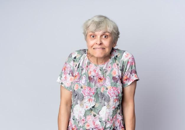 불안 노인 여성 스탠드에 고립 된 흰색 벽
