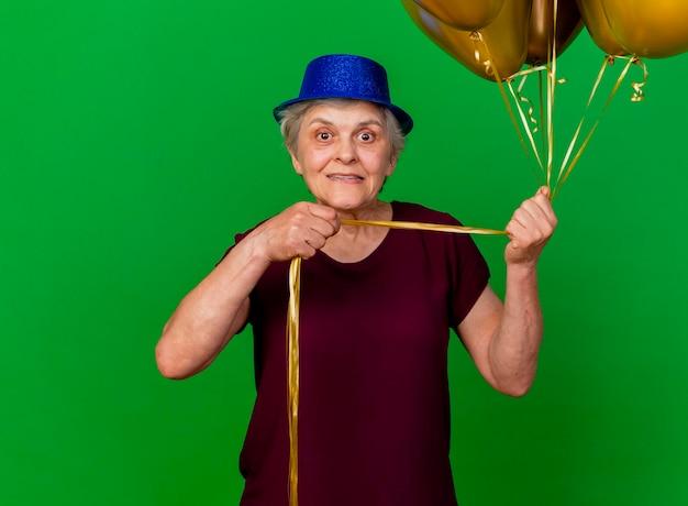 La donna anziana ansiosa che porta il cappello del partito tiene i palloni dell'elio sul verde