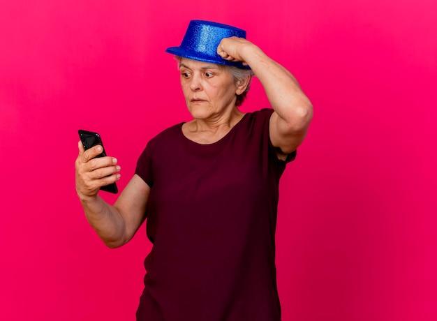 パーティーハットをかぶって気になる年配の女性はピンクの電話を見て頭に拳を置きます