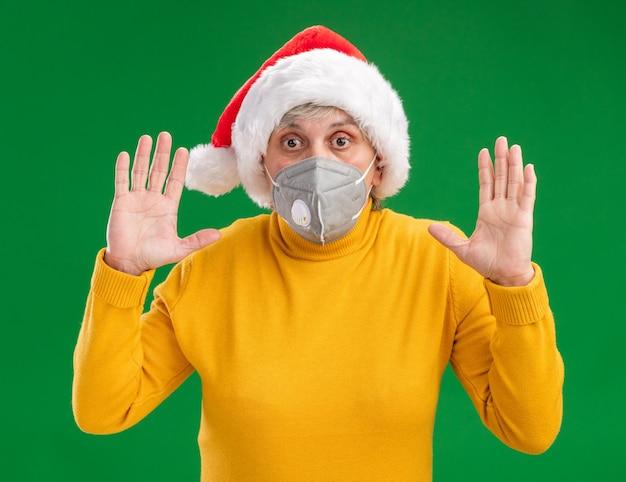コピースペースと緑の壁に隔離された上げられた手で立っている医療マスクを身に着けているサンタ帽子を持つ気になる年配の女性