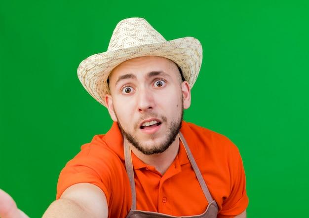 Giardiniere ansioso uomo che indossa il cappello da giardinaggio pretenfd da tenere e guarda