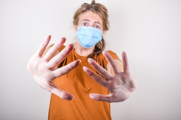 医療マスクと茶色のtシャツの気になる女の子は、白い壁に分離された彼女の手で停止信号を示しています。女の子は家にいることを勧めます。