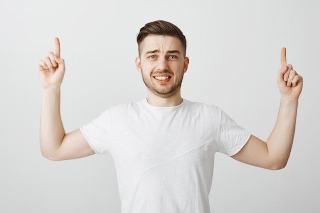 Ansioso smorfie ragazzo che punta le dita verso l'alto con la faccia spaventata