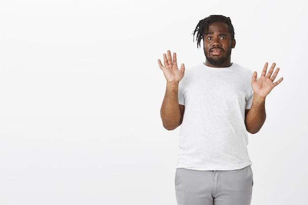 Обеспокоенный парень с косами позирует у белой стены