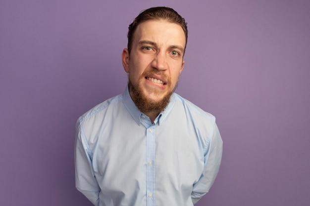 Uomo biondo bello ansioso morde le labbra isolate sulla parete viola