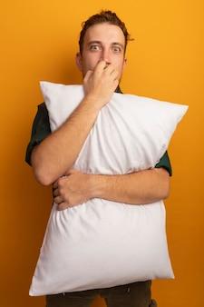 불안한 잘 생긴 금발의 남자가 손톱을 물고 오렌지 벽에 고립 된 베개를 보유하고 있습니다.