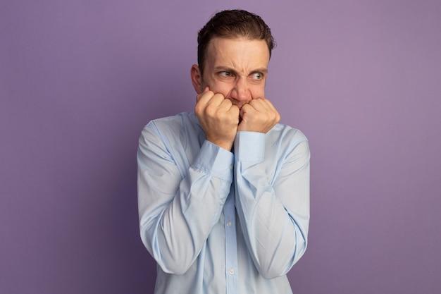 気になるハンサムなブロンドの男が爪を噛み、紫色の壁に隔離された側を見て