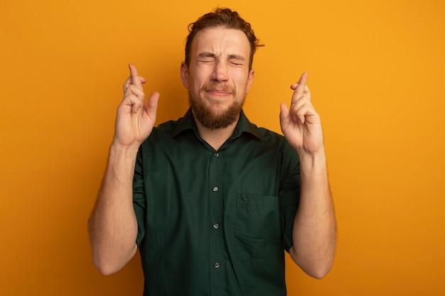 Uomo biondo bello ansioso sta con gli occhi chiusi che incrociano le dita isolate sulla parete arancione