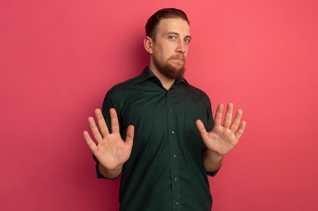 Uomo biondo bello ansioso sta con le mani alzate isolate sulla parete rosa