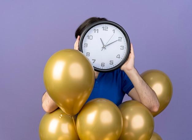 Un bell'uomo caucasico ansioso sta con palloncini di elio che tengono l'orologio davanti al viso