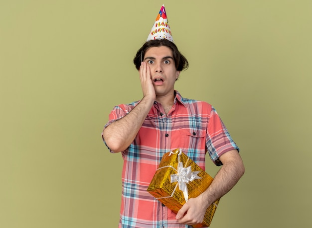 Anxious handsome caucasian man wearing birthday cap puts hand on face and holds gift box