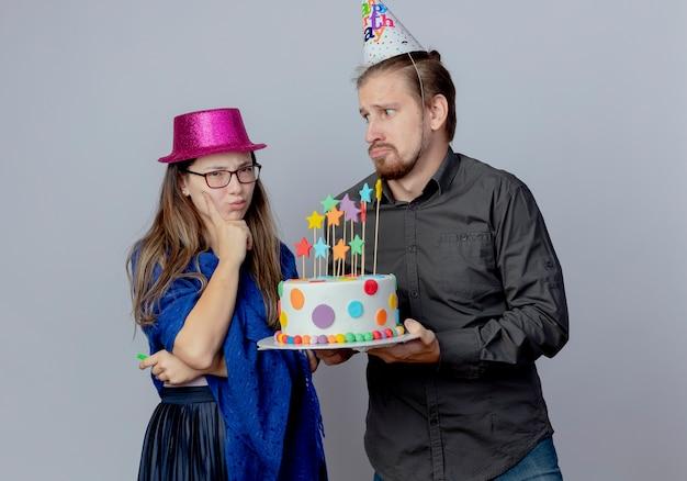 L'uomo bello ansioso in berretto di compleanno che tiene la torta e guardando la ragazza infastidita con gli occhiali che indossa il cappello rosa tiene il fischio e mette la mano sul mento isolato sul muro bianco