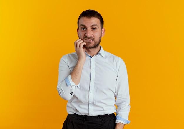 L'uomo bello ansioso morde le labbra mette la mano sul mento che sembra isolato sulla parete arancione