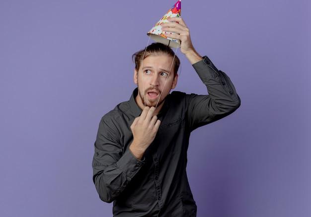 불안한 잘 생긴 남자는 보라색 벽에 고립 된 측면을보고 머리 위에 생일 모자를 보유