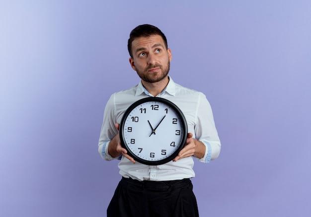 気になるハンサムな男は、紫色の壁に隔離された側を見て時計を保持します。