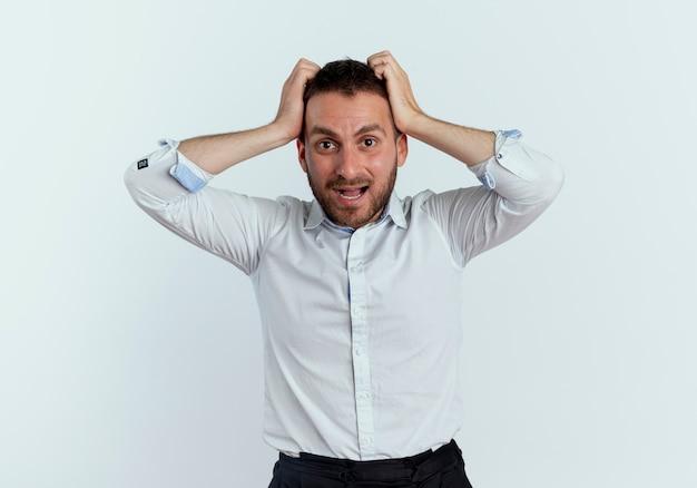 気になるハンサムな男は白い壁に孤立して見える頭を保持します