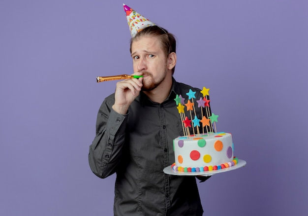 생일 모자에 불안 잘 생긴 남자는 보라색 벽에 고립 된 휘파람을 불고 케이크를 보유하고