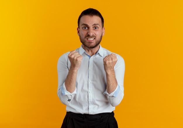 気になるハンサムな男は、オレンジ色の壁に拳を隔離し続けます