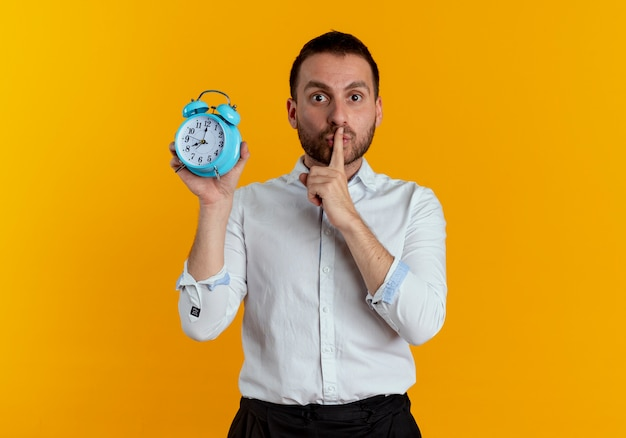 불안한 잘 생긴 남자는 오렌지 벽에 고립 된 알람 시계를 들고 자장 조용한 몸짓 입에 손가락을 넣습니다.